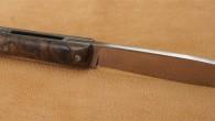 Couteau de type liner lock. Lame Niolox – manche Noyer – guillochage. Longueur de lame : 9,3 cm. Longueur totale : 21,3 cm.