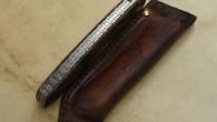 Couteau de type liner lock. Lame RWL34– plaquettes en loupe de noyer stabilisé– platines titane – guillochage. Pochette en cuir moulé. Longueur de lame : 9,2cm. Longueur totale : 19,5cm.