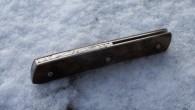 Couteau de type liner lock. Lame RWL34– plaquettes Noyer stabilisé– platines titane – guillochage poissons. Longueur de lame : 9,6cm. Longueur totale : 20,8 cm.
